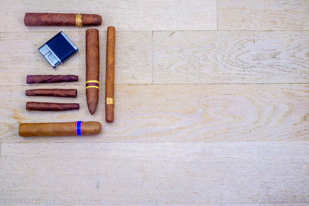 Cuban cigars and a lighter on a wooden floor Reklamní fotografie