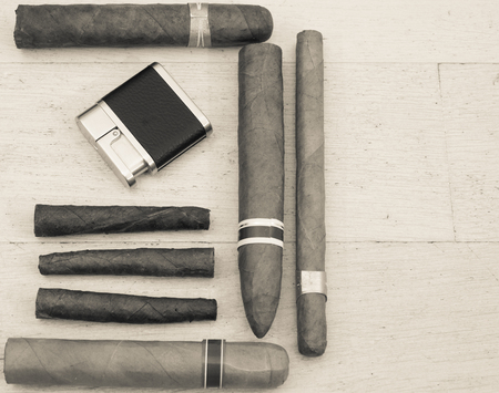 Cuban cigars and a lighter on a wooden floor. Vintage style