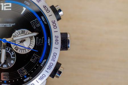 One wristwatch on wooden background
