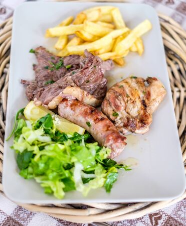 Dish with three kinds of meat, salad and chips. Vertical
