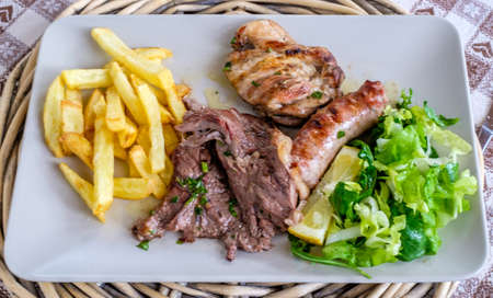 Dish with three kinds of meat, salad and chips. Horizontal Reklamní fotografie