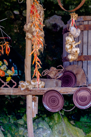 chili, garlic and onions hanging in a cave with earthenware bowls