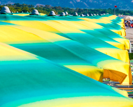 Row of colorful umbrellas on a Mediterranean beach. Ionian Sea, Calabria. Italy Reklamní fotografie
