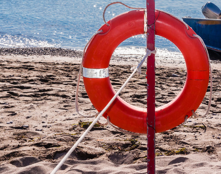 Red lifebelt on the beach. Ionian Sea, Calabria. Italy
