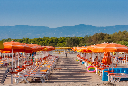 Beach with rows of orange umbrellas. Ionian Sea, Calabria. Italy