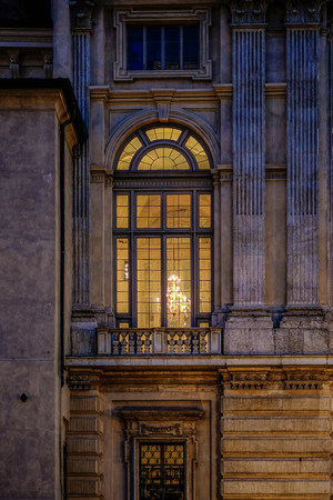 lighted: Large Madama palace lighted window by a chandelier. Turin, Italy Editorial