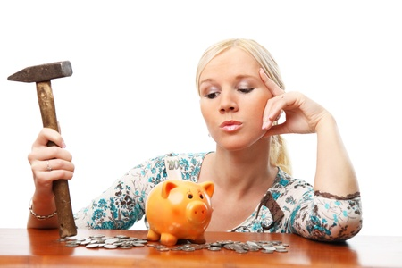 Portrait of attractive woman thinking to break a piggy bank. Isolated over white background.