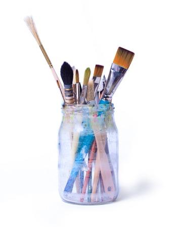 Verf kunst borstels in een glazen pot geïsoleerd op een witte achtergrond.