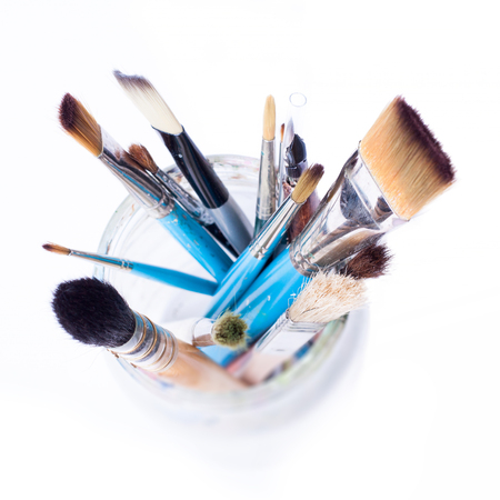 Artist brushes in a glass jar - view from the top. Isolated over white background. 版權商用圖片