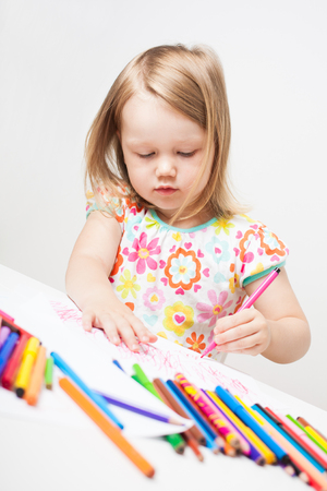 Cute little girl drawing with colourful pencils and markers. 版權商用圖片