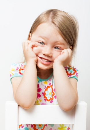 Beautiful funny smiling little girl on light gray background.