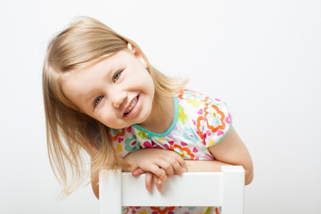 Funny smiling little girl sitting on a chair. Isolated over light gray background.
