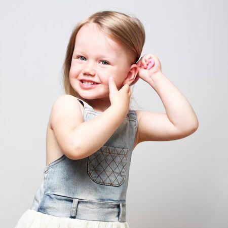 Beautiful cute little girl combing her hair over light gray background 版權商用圖片