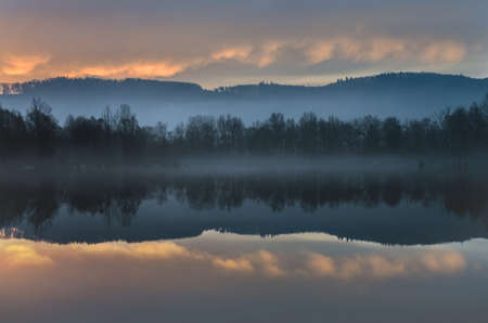 alpenglow: Lake at dawn, trees reflected in a water,alpenglow over the landscape. Stock Photo