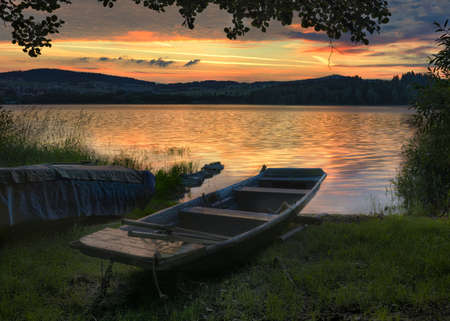 lipno: Rowboat on beautiful lake with dramatic sunset.The morning of the loch.Landscape with boat.A fishing boat tied at the shore of a Lipno lake Czech Republic.Nature landscape.