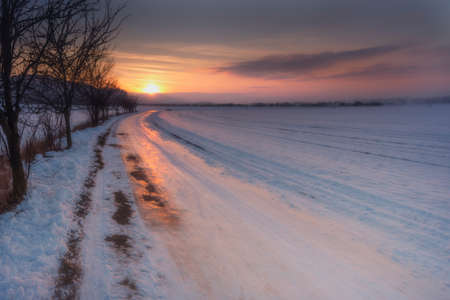 Winter landscape snowy path and sunset.Sunset over the winter landscape.