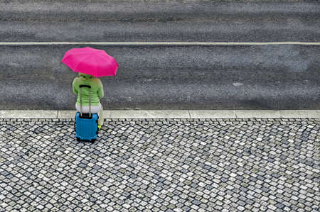 Woman with umbrella and suitcase waiting near road. Zdjęcie Seryjne