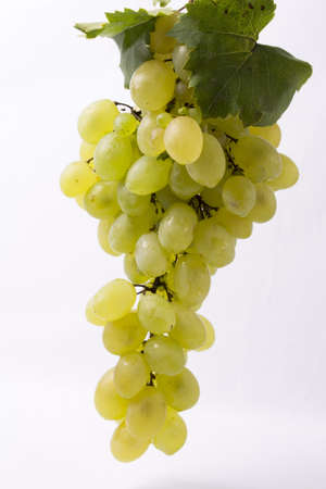 a clove of white table grapes, green leaves on white background