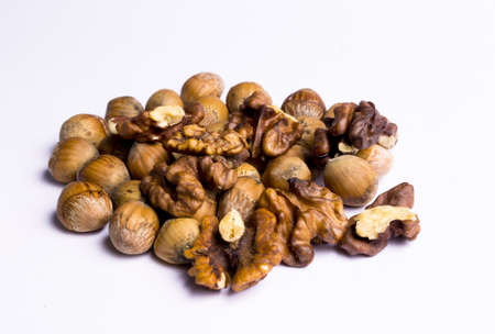 hazelnuts and walnuts in a heap on white background Stock Photo