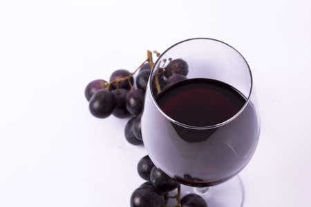 a glass of red wine and grape over white