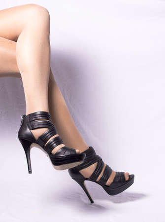 Legs with black high heels. white background