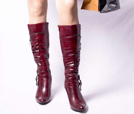 Red womens boots, bags of shopping in white background