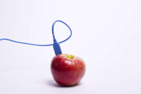 red apple with a USB cable connected to the blue