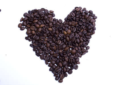 coffee grains formed heart shape on white background
