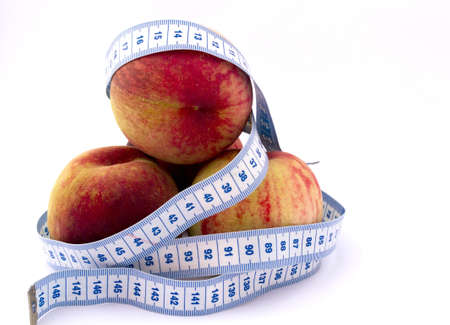 peach surrounded by piles of blue tape on white background, healthy weight loss