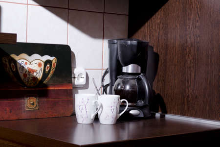 coffee makers and two cups of coffee scoop in the morning sun
