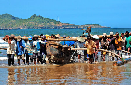 Fishermen of Patai Telengria holding a boat from the beach in Pacitan, East Java, Indonesia