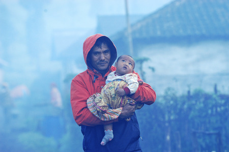 A father holding his son in Ranupane on the slopes of Mount Semeru, Lumajang, East Java, Indonesia. Photo katen on May 29th, 2009.
