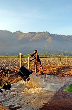 irrigate: Farmers irrigate their fields of dry season in Pacitan, East Java, Indonesia