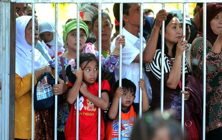 Banyuwangi people behind the fence to watch the carnival in town