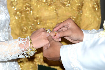 Bride and groom hands and wedding ring exchange.