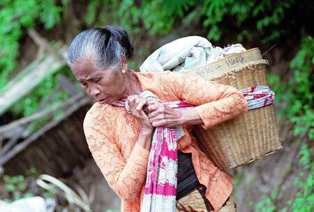 shouldered: Javanese women in the village Ngebel shouldered rinjing (bags made of bamboo) around Lake Ngebel, Ponorogo, East Java, Indonesia. Photo taken June 12th, 2003.