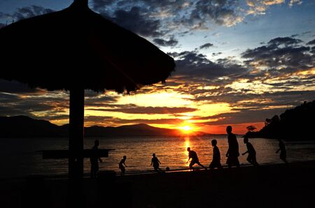alongside: childrens playing alongside a Kelapa Beach DIli Titor Leste
