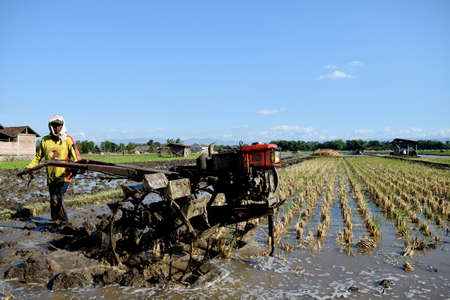 golan: Farmer plowing his field with a tractor in Golan Village, Sampung, Ponorogo, East Java, Indonesia. Editorial