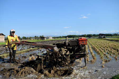 golan: Farmer plowing his field with a tractor in Golan Village, Sampung, Ponorogo, East Java, Indonesia