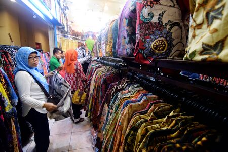 A woman choosing clothes in a shopping mall Jembatan Merah Plaza Surabaya, East Java, Indonesia Editorial