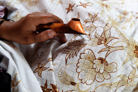 Painting watercolor on the fabric to make Batik is part of Indonesian culture 版權商用圖片