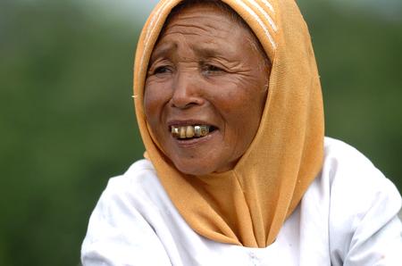 A Javanesse old lady seling flower Edelweis at Mount Merapi, Yogyakarta, DIY Yogyakarta, Indonesia on July 21, 2007