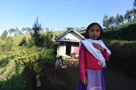 A tengger tribe girl welcomes tourist arrivals in front of her house that will climb the peak at Argosari village, semeru mountain slopes, Lumajang, east java, Indonesia on May 22, 2016