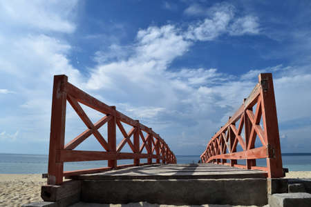 Wooden bridge to the beach against a dramatic sky backdrop 写真素材