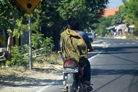 The characteristic of Indonesian men in rural areas is wearing sarong everywhere, as in the picture of the man in Bangkalan, Madura, Indonesia wearing a sarong while riding a motorbike. Photo taken on