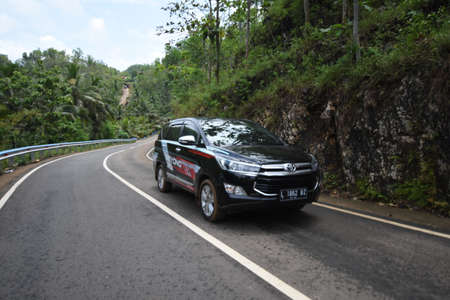 Pacitan, Indonesia - September 24, 2016: The latest Toyota Innova black car (model 2016) in a test drive on a mountain road in Pacitan, East Java, Indonesia 写真素材 - 156973472