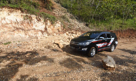 Pacitan, Indonesia - September 24, 2016: The latest Toyota Innova black car (model 2016) in a test drive on a mountain road in Pacitan, East Java, Indonesia