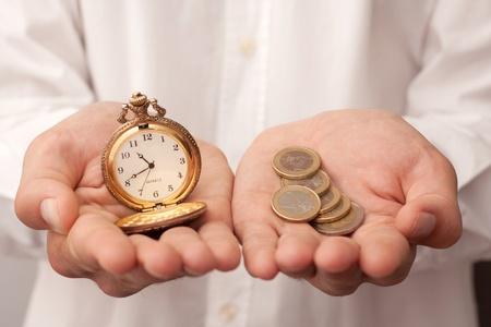 organise: hombre que sostiene un reloj de bolsillo y dinero Foto de archivo
