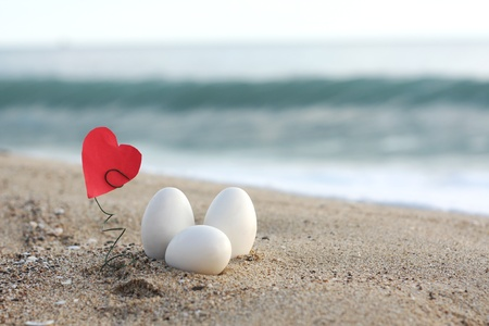 three white easter eggs on the sandy beach Фото со стока - 9343915