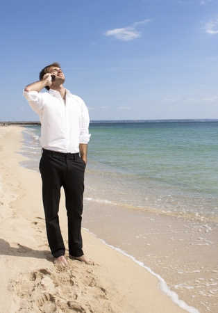 young man is having pleasant telephone conversation on the beach photo